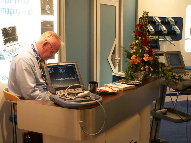 мъж на щанд, показващ ехокардиограф
